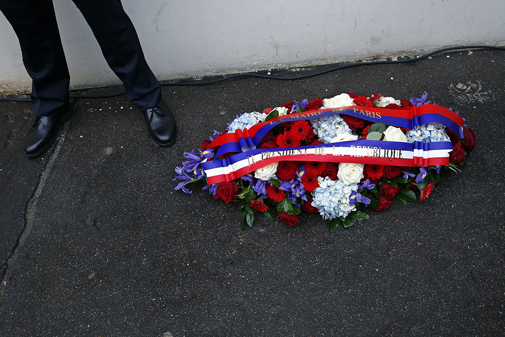 """A wreath of flowers from the French President and Paris Mayor is seen January 5, 2016 during a ceremony to unveil a commemorative plaque to pay tribute to the victims of the last year's January attacks outside the former offices of French weekly satirical newspaper Charlie Hebdo in Paris. A total of 17 people were killed in the three days of attacks dubbed """"France's 9/11"""", marking the start of a string of jihadist strikes in the country that culminated in November's massacre in Paris. / AFP / POOL / BENOIT TESSIER"""