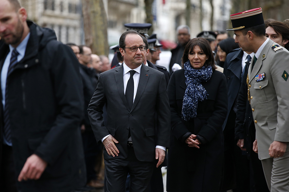 "French President Francois Hollande (C) and Paris Mayor Anne Hidalgo attend a ceremony to unveil a commemorative plaque at the site where policeman Ahmed Merabet was killed during the last year's January attack in Paris on January 5, 2016. A total of 17 people were killed in the three days of attacks dubbed ""France's 9/11"", marking the start of a string of jihadist strikes in the country that culminated in November's massacre in Paris. / AFP / POOL / BENOIT TESSIER"