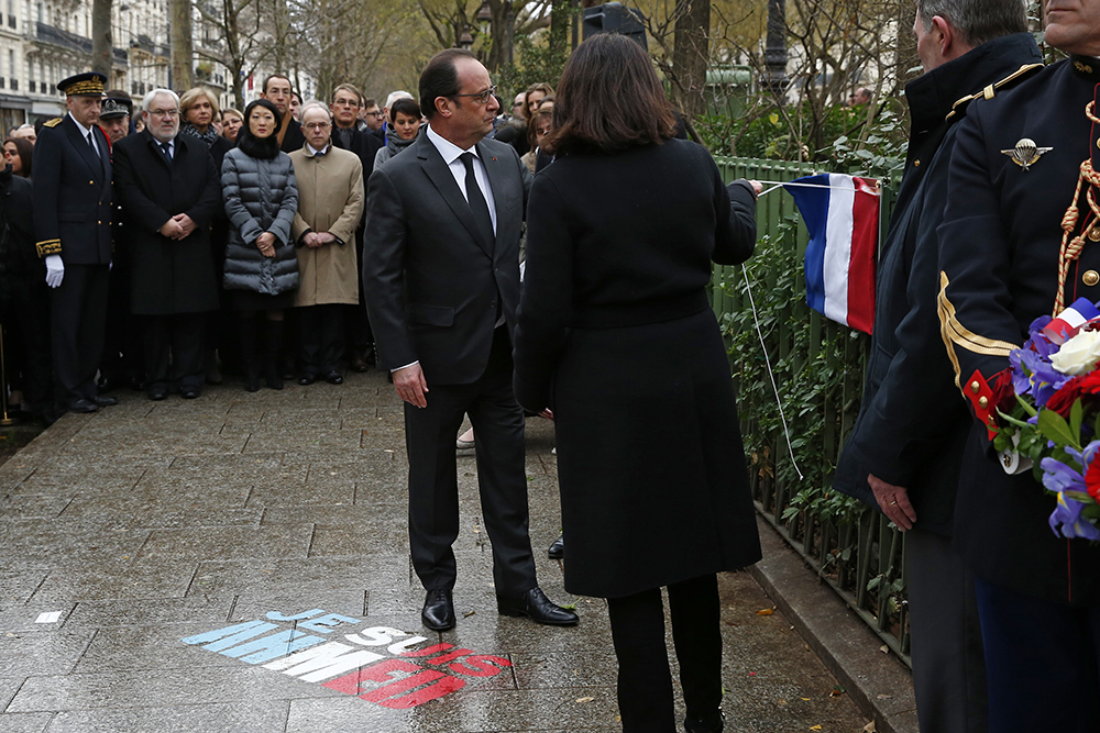 "French President Francois Hollande (C) and Paris Mayor Anne Hidalgo unveil a commemorative plaque on January 5, 2016 during a ceremony at the site where policeman Ahmed Merabet was killed during the last year's January attack in Paris. A total of 17 people were killed in the three days of attacks dubbed ""France's 9/11"", marking the start of a string of jihadist strikes in the country that culminated in November's massacre in Paris. / AFP / POOL / BENOIT TESSIER"