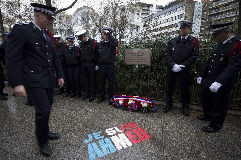 """Police officers stand near the message """"I am Ahmed"""" painted on the ground on January 5, 2016 during a ceremony to unveil a commemorative plaque at the site where policeman Ahmed Merabet was killed during the last year's January attack in Paris. A total of 17 people were killed in the three days of attacks dubbed """"France's 9/11"""", marking the start of a string of jihadist strikes in the country that culminated in November's massacre in Paris. / AFP / JOEL SAGET"""