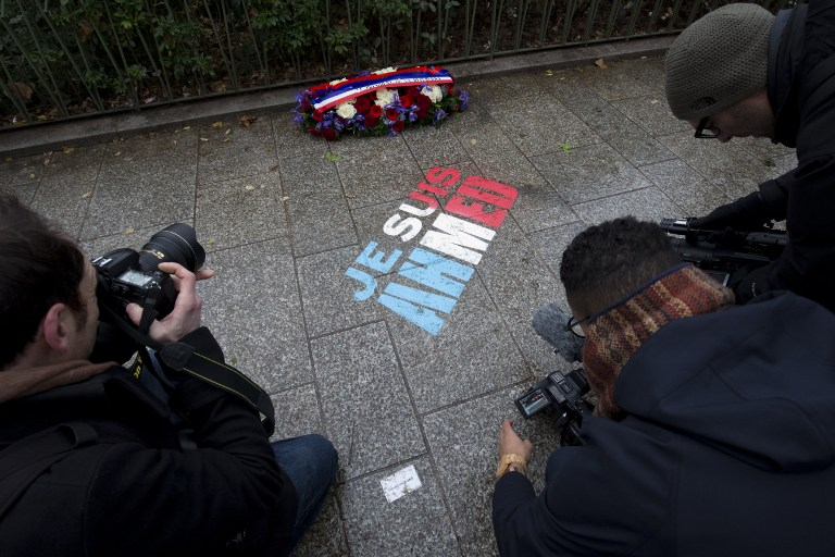 """Photographers and cameramen take pictures of the message """"I am Ahmed"""" painted on the ground on January 5, 2016 during a ceremony to unveil a commemorative plaque at the site where policeman Ahmed Merabet was killed during the last year's January attack in Paris. A total of 17 people were killed in the three days of attacks dubbed """"France's 9/11"""", marking the start of a string of jihadist strikes in the country that culminated in November's massacre in Paris. / AFP / JOEL SAGET"""