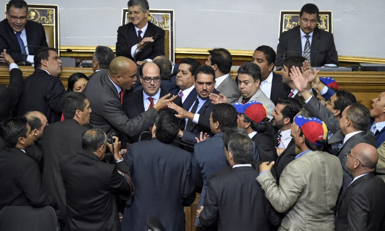 Newly elected opposition deputy Julio Borges (C) and governement deputy Hector Rodriguez (2nd L) argue during the new parliament's swearing-in ceremony in Caracas, on January 5, 2016. Venezuela's President Nicolas Maduro ordered the security forces to ensure the swearing-in of a new opposition-dominated legislature passes off peacefully Tuesday, after calls for rallies raised fears of unrest. AFP PHOTO/JUAN BARRETO / AFP / JUAN BARRETO