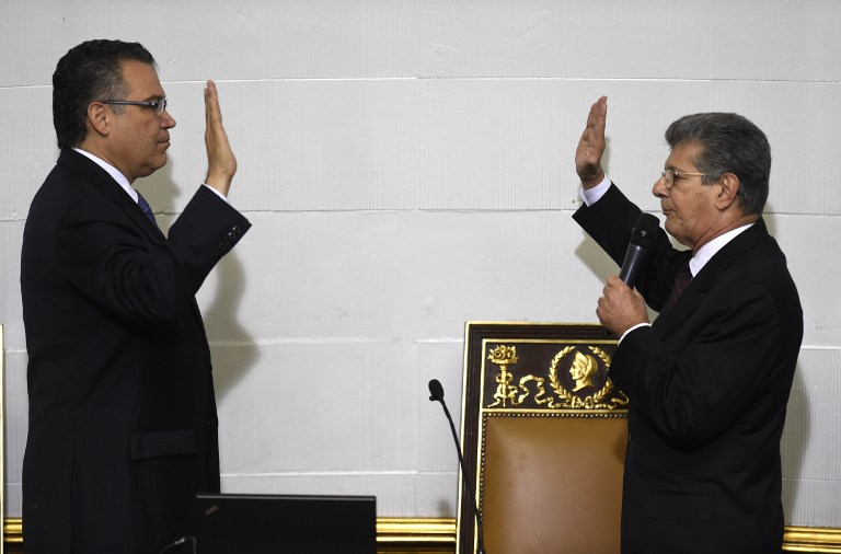The new president of the Venezuelan parliament, Henry Ramos Allup (R), takes the oath from first vice president Enrique Marquez, during the swearing-in ceremony in Caracas, on January 5, 2016. Venezuela's President Nicolas Maduro ordered the security forces to ensure the swearing-in of a new opposition-dominated legislature passes off peacefully Tuesday, after calls for rallies raised fears of unrest. AFP PHOTO/JUAN BARRETO / AFP / JUAN BARRETO