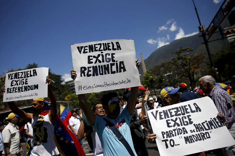 "Opposition supporters hold signs during a rally against Venezuela's President Nicolas Maduro's government in Caracas, March 12, 2016. The signs read, (L-R) ""Venezuela calls for referendum"", ""Venezuela calls for (Maduro's) resignation"" and ""Venezuela calls for the birth certificate of Maduro"". REUTERS/Carlos Garcia Rawlins"