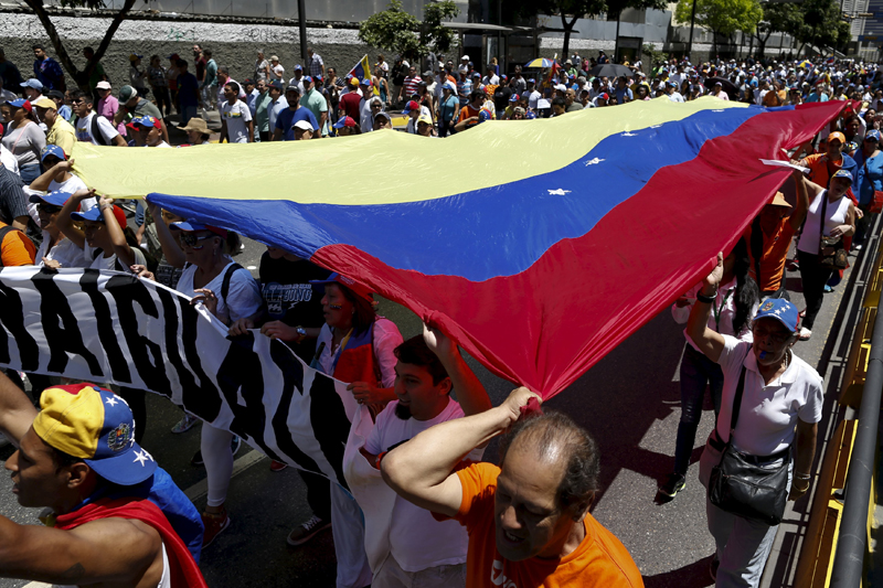 Opposition supporters carry a giant Venezuelan flag during a rally against Venezuela's President Nicolas Maduro's government in Caracas, March 12, 2016. REUTERS/Carlos Garcia Rawlins