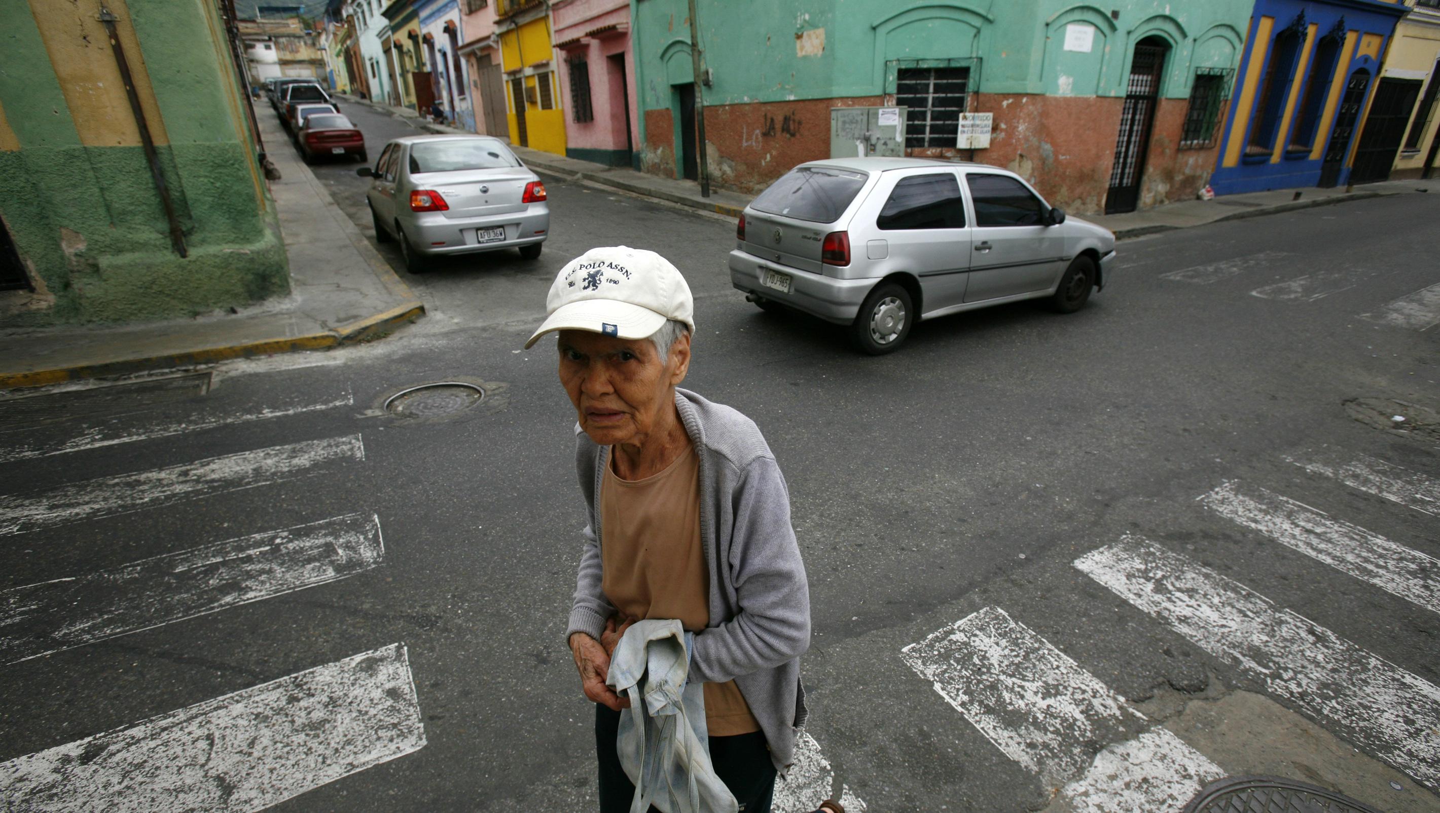 Durante el paseo por las calles de La Pastora, numerosos vecinos paran a la encargada de Fundapatrimonio en la zona, Jacqueline Mogollón, para exigir que arreglen sus casas mientras ella lamenta el retraso de los nuevos recursos prometidos para el proyecto.