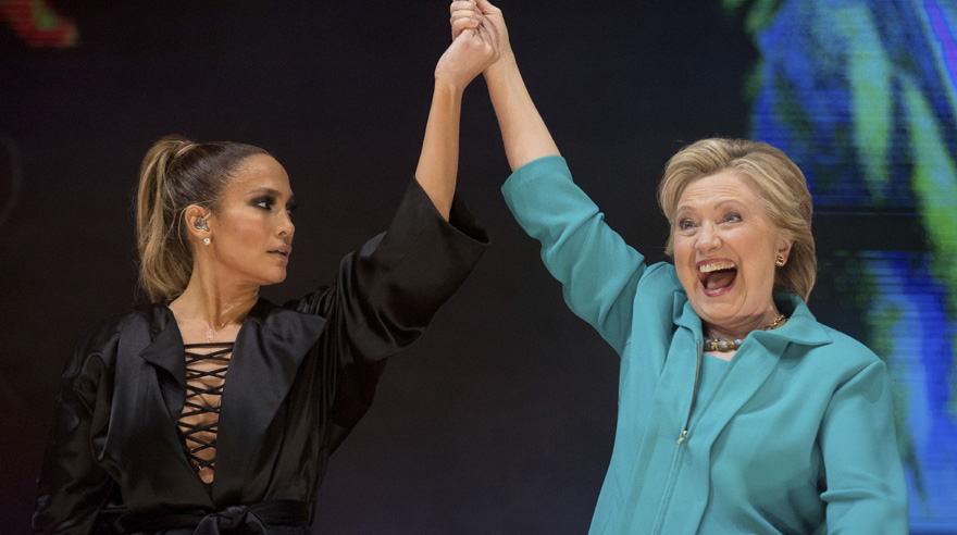 Democratic presidential candidate Hillary Clinton, right, takes the stage with performer Jennifer Lopez, left, at a Get Out The Vote performance at Bayfront Park Amphitheater in Miami, Saturday, Oct. 29, 2016. (AP Photo/Andrew Harnik)